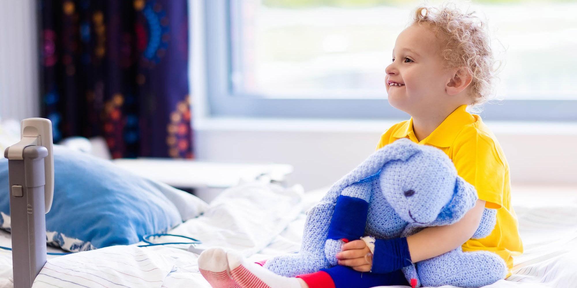 Lachend kind, met blauwe knuffel in hand en geel shirt aan, in ziekenhuisbed