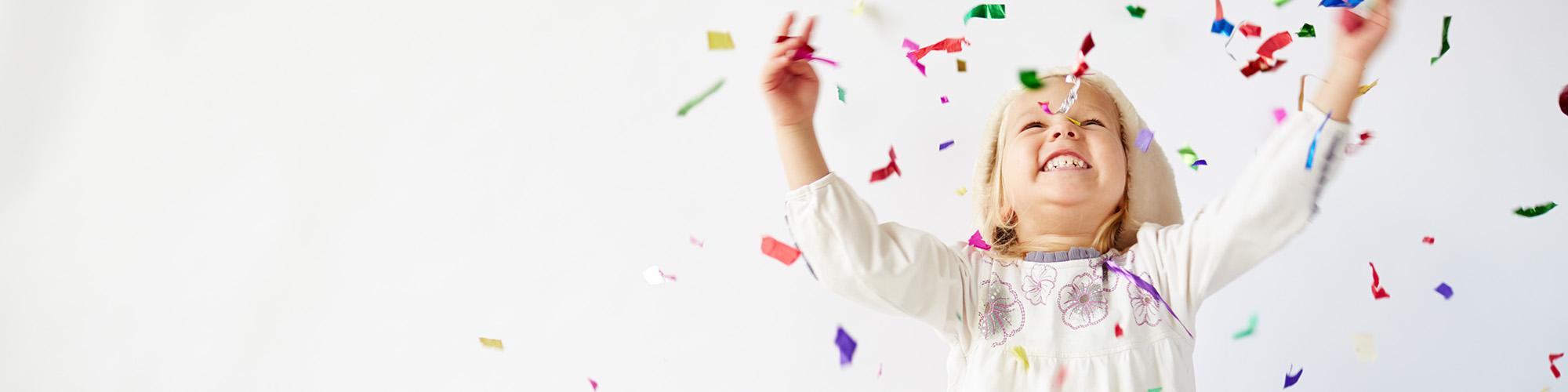Vrolijk, juichend meisje dat confetti in de lucht gooit