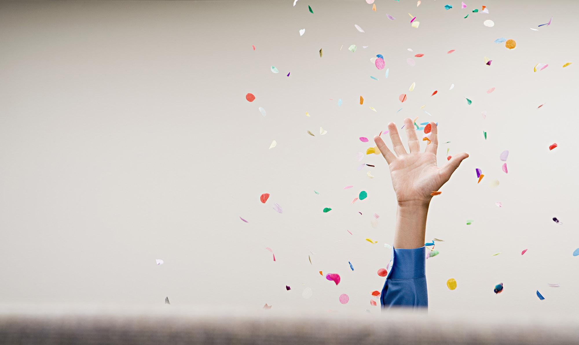 Uitstekende, open hand, omgeven door confetti